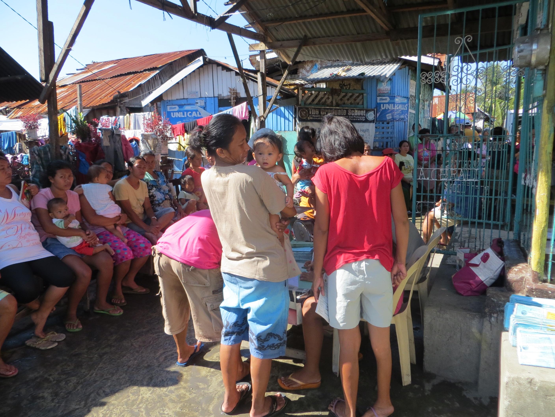 Wartende Patienten vor einer kleinen Kapelle im Slumgebiet Sawsawan