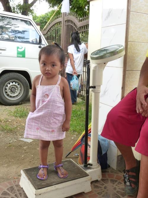 Kleines philippinisches Mädchen beim Wiegen