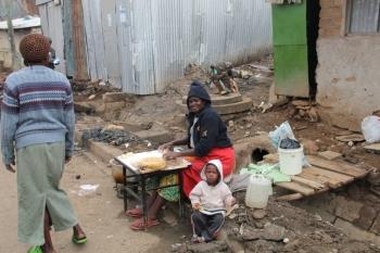 Frauen bereiten mitten im Slum Essen zum Verkauf zu